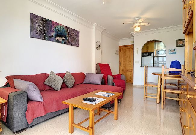 living room with sofa, dining table and chairs, tv and air conditioning